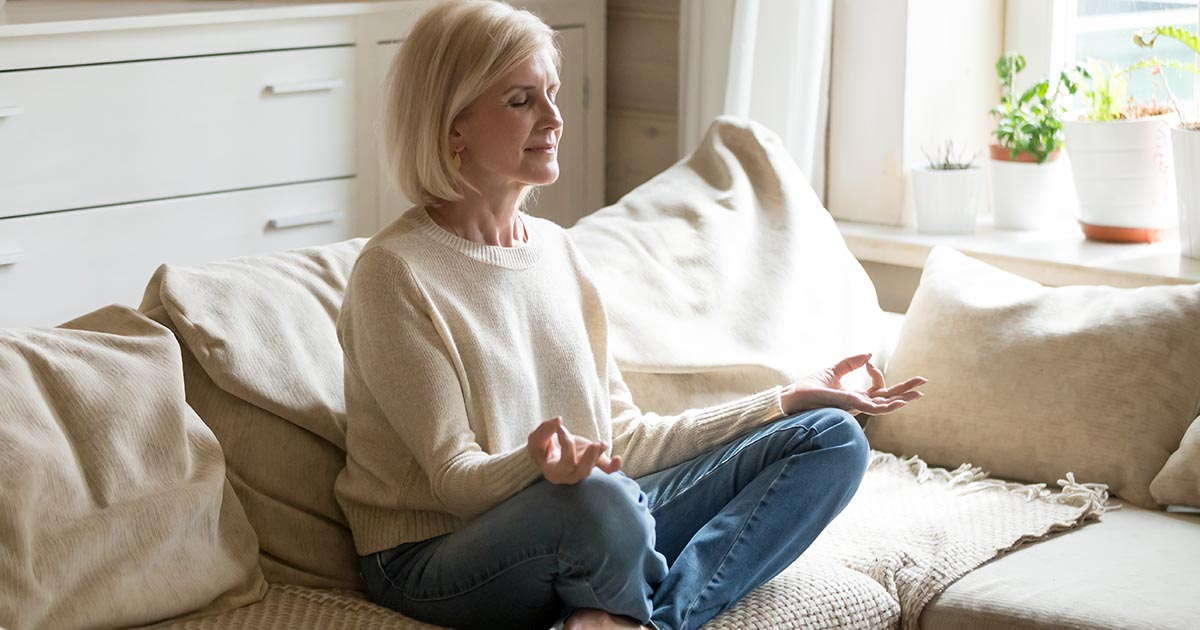 Mindful mature woman practicing yoga meditation at home