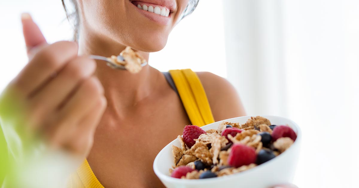 Woman eating cereals and fruits at home
