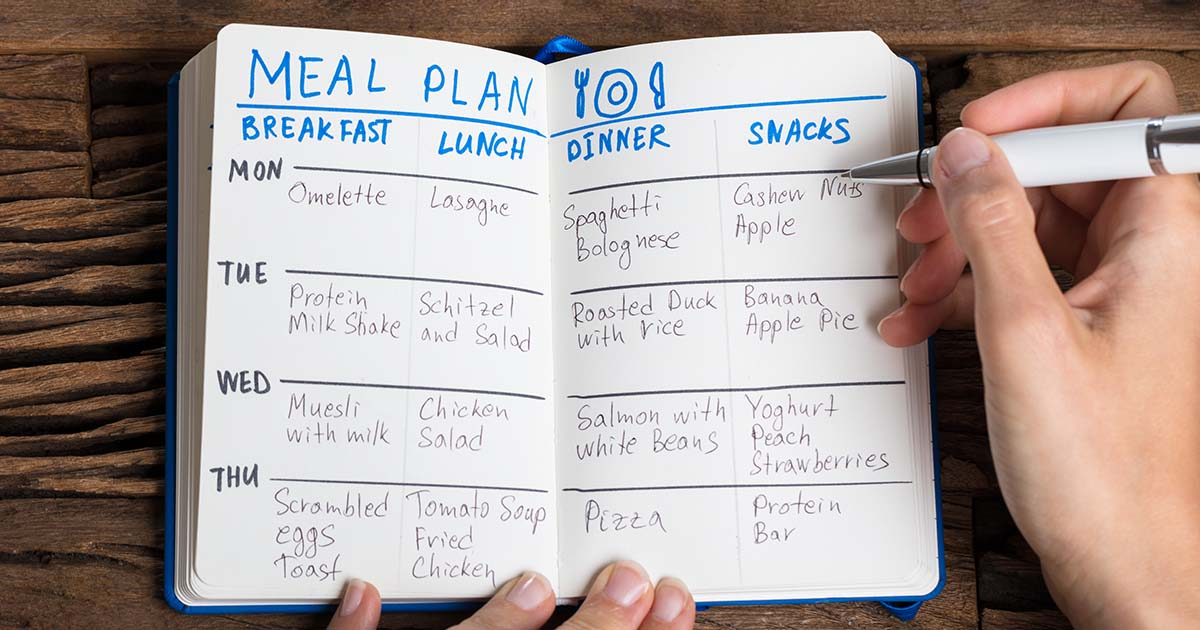 Person filling out meal plan notebook