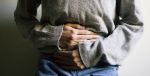 a woman with inflamed bowels, holding her stomach in pain